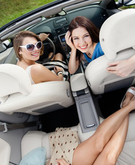 Top view of happy women with sunglasses sitting in the car