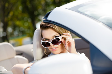 Pretty woman taking sunglasses  in the cabriolet