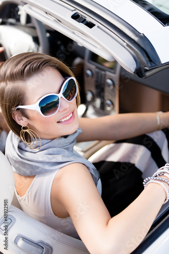 Pretty woman wearing sunglasses with white rim turns back