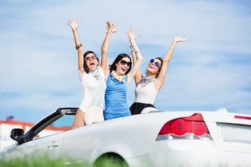 Group of girls stands in the automobile with hands up