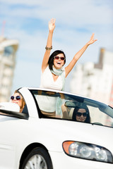 Lovely teenager with her hands up in the car with friends