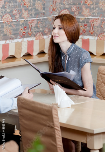 Woman holds the menu choosing a dish to make an order