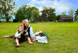 Little boy and girl sitting on a lawn in a national latvian clot