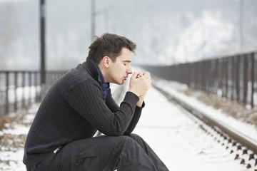 Sad man in railroad track