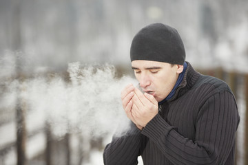 Young man in winter landscape and warmed the hands of breath