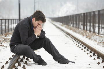 Sad man in railroad track