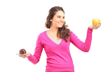 Woman holding an apple and a cake and trying to decide which one