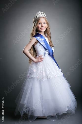 Pretty little girl in tiara and long white dress