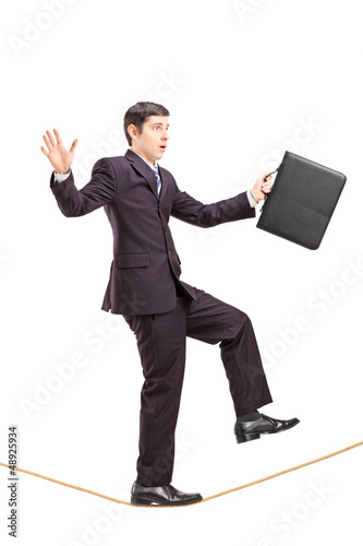 Full length portrait of a businessman with briefcase walking on