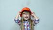 Orange rain. Girl in the construction helmet. Falling tangerines