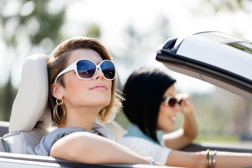 Close up of girls wearing sunglasses in the white car