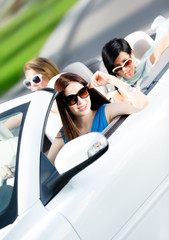 Group of happy teenagers driving the car