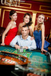 Man surrounded by girls gambles roulette at the casino