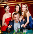 Man surrounded by women plays roulette at the gambling house