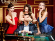Girls cover the eyes of the gambler playing roulette