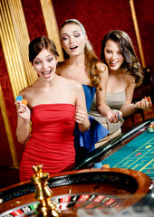 Three women playing roulette at the casino