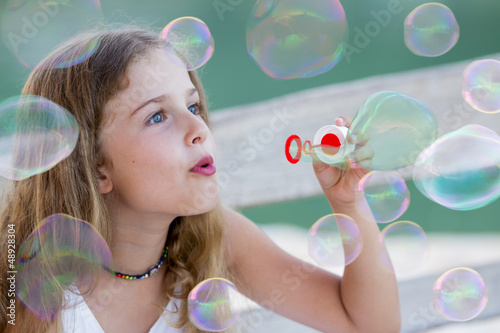 Summer joy - lovely girl blowing soap bubbles