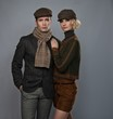 Elegant couple in caps isolated on grey background