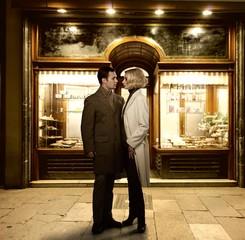 Elegant couple against bakery shop window
