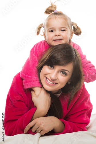Happy mother and daughter in dressing gowns