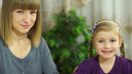 Mother and daughter at the table looking at camera
