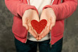 Closeup  of teen girl in pink hoodie holding red heart