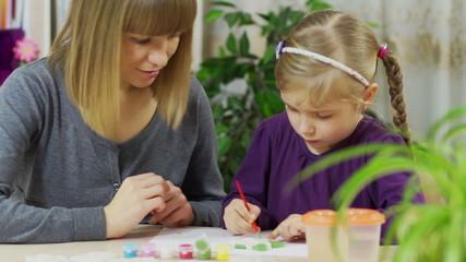 Mother teaches a child to paint. The girl is engaged in drawing