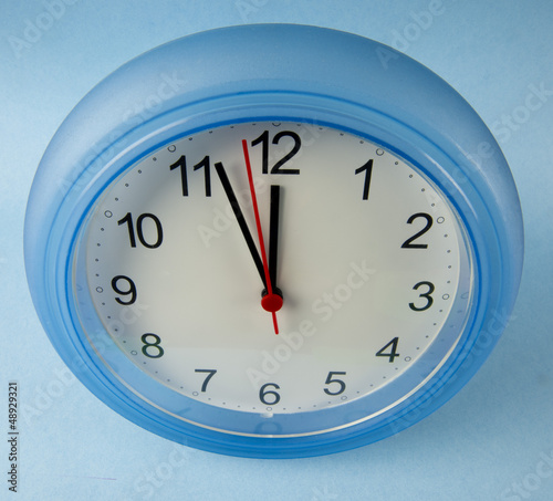 Clock midnight or noon on blue background