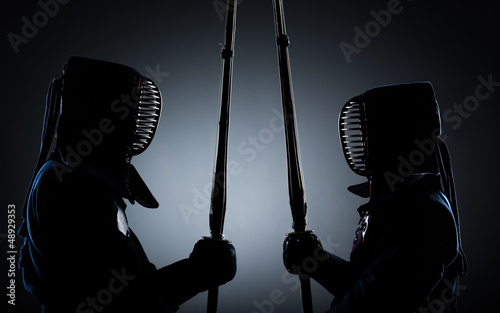 Two kendo fighters opposite each other with shinai