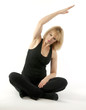 Mature, pretty  blond woman doing yoga stretching exercise