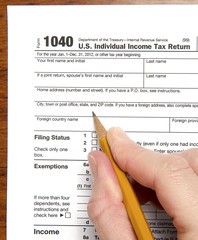 United States tax form with hand holding  pencil