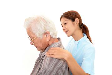高齢者の肩もみをする介護士