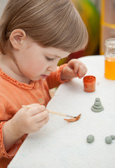 Beautiful little girl covers with drawings clay toys