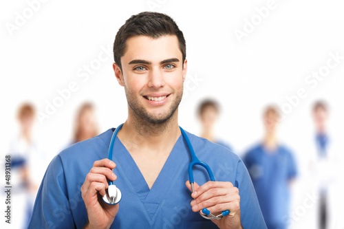 Handsome doctor in front of his team