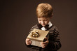 Child holding gift box and looking at present. Vintage style.