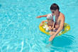 son with his father on a yellow circle swimming in a pool with c