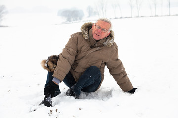Senior man with injured leg on snow
