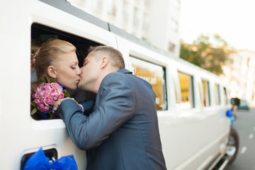 couple in love bride and groom posing at car window