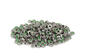 heap of metal nuts with green interior, stacked