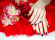 Woman beautiful manicured hands lying down with flowers on red
