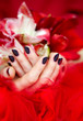 Cupped hands with dark manicure holding bright flowers