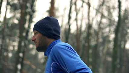 Lone runner in wintry wood, slow motion shot at 240fps, crane sh