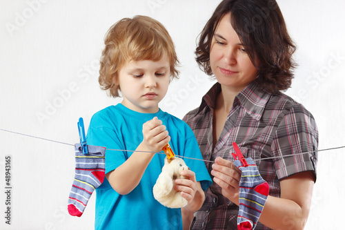 Little boy helps her mother to hang up your toy and socks