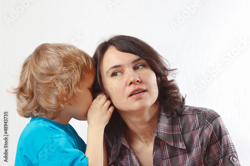 A little cute boy whispers something to his mother