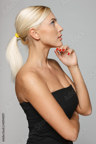 Side view of beautiful blond pensive woman with hand on chin