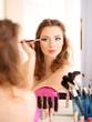 Young beautiful woman making make-up near mirror