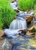 Fast river among stones cascades. Natural landscape