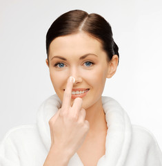 woman in bathrobe applying creme