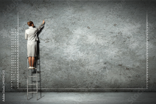 businesswoman drawing diagrams on wall