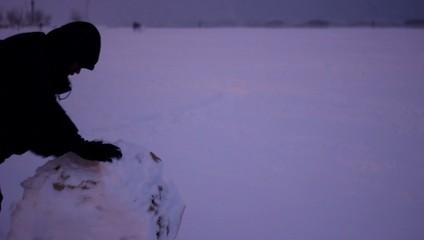 ragazzo spinge palla di neve in inverno al freddo